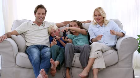 дичь : Happy family playing video games at home on the sofa