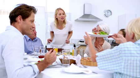 vacsora : Woman serving salad at dinner to extended family at home in kitchen