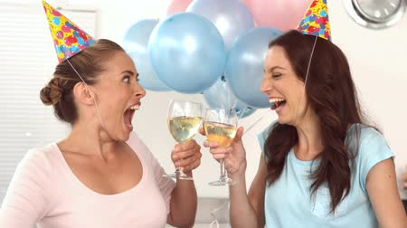 léggömb : Women clinking their flutes of champagne for a birthday with party hats, party horn and balloons in slow motion  Stock mozgókép