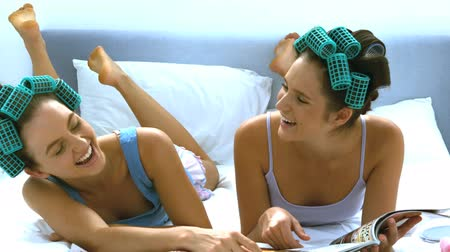 pont : Friends with hair roller laughing while reading a tabloid in the bed in slow motion  Stock mozgókép