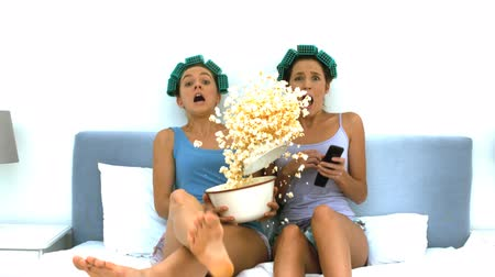pipoca : Friends watching TV together and throwing popcorn in slow motion  Stock Footage