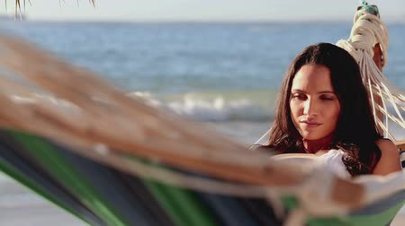 гамак : Cute brunette woman reading a book on a hammock on the beach