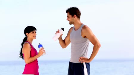 atletismo : Man and woman drinking water on the beach after sport