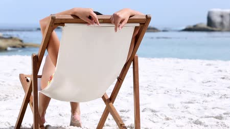 bronzlaşma : Woman sitting and tanning on a chair on the beach