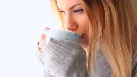 pulóver : Attractive blonde in winter clothes holding mug of coffee on bright background