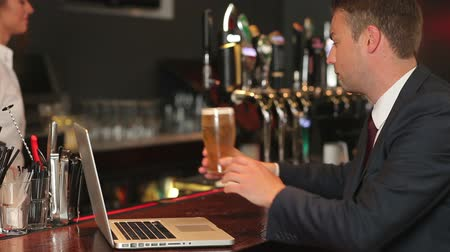 focus pull : Businessman working on his laptop while having a beer in a pub