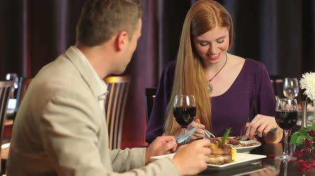 vacsora : Loving couple talking while having dinner together in a classy restaurant Stock mozgókép