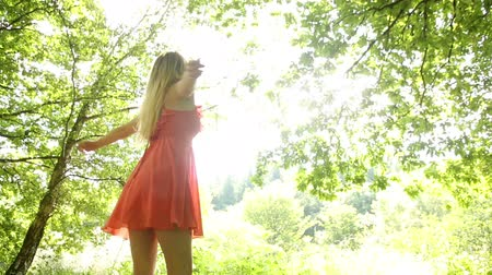 éteri : Beautiful teen twirling in the sunlight under the trees in a forest Stock mozgókép