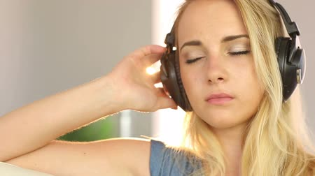 наушники : Beautiful blonde teen relaxing and listening to music in her sitting room at home Стоковые видеозаписи