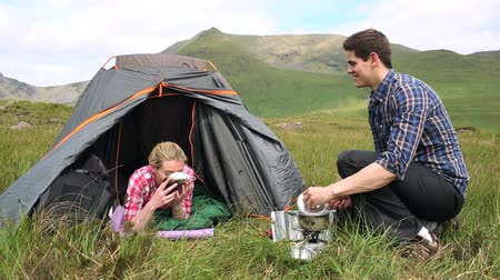 kamp : Man handing his girlfriend a bowl of soup on a camping trip in the countryside Stok Video