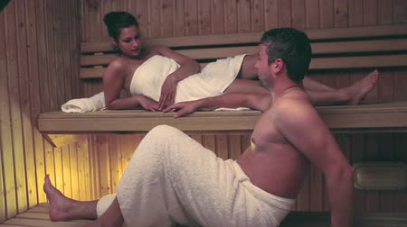 sıcak : Couple relaxing and chatting together in a sauna at the hotel spa Stok Video