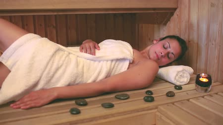 towel : Brunette wearing a towel relaxing in the sauna at the hotel spa Stock Footage