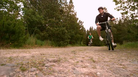 bicycle : Athletic couple mountain biking in the countryside together in slow motion