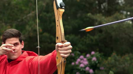 nyíl : Man shooting bow and arrow in slow motion Stock mozgókép