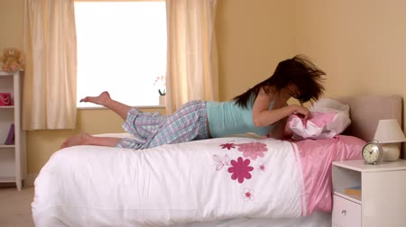pizsama : Attractive young woman jumping on her bed in a bedroom in slow motion Stock mozgókép