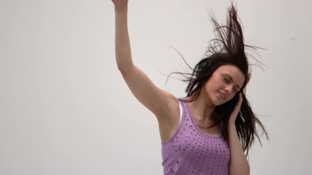 наушники : Cute young woman jumping while listening to music on white background in slow motion