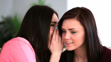 pletyka : Attractive woman telling her friend a secret in the living room