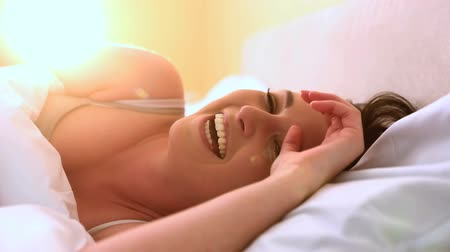 smích : Pretty woman giggling in bed in the bedroom Dostupné videozáznamy