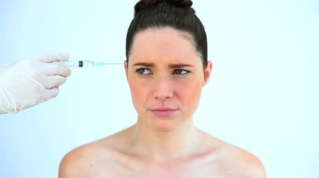 operacja plastyczna : Hand putting a syringe on the forehead of a troubled woman against white background