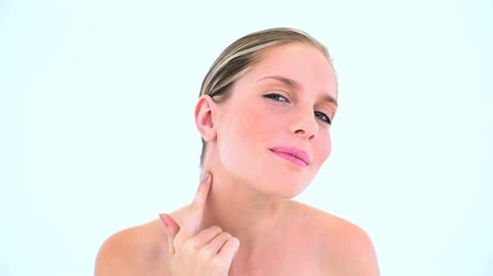 cuidados com a pele : Pretty woman spreading cream on her neck against white background Stock Footage