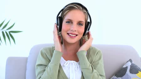 sluch : Woman wearing headphone and listening to music on couch Dostupné videozáznamy