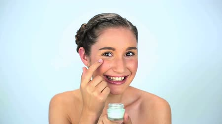 hydratují : Young woman applying cream on her face on white background