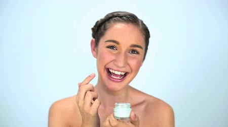 hydratují : Smiling young woman applying cream on her face on white background