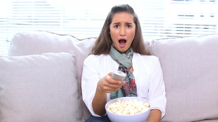 потрясенный : Brunette watching television and eating popcorn on sofa Стоковые видеозаписи