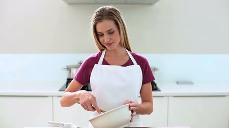 kötény : Smiling blonde woman preparing cake in kitchen at home Stock mozgókép