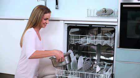ajoelhado : Blonde woman put her dishes in dishwasher and does a thumbs up in kitchen at home Vídeos