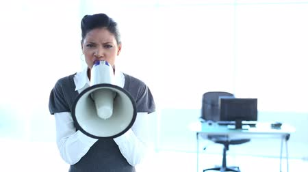 boxe : Serious businesswoman screaming in a megaphone in office