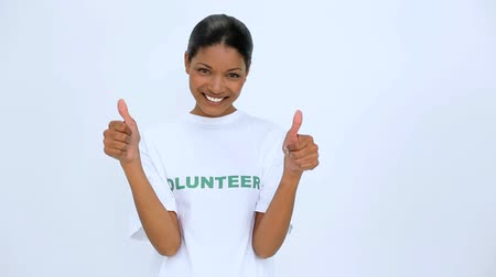 wolontariat : Smiling volunteer woman does a thumbs up at camera on white background