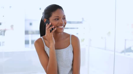 telefone celular : Beautiful woman calling someone with her mobile phone in apartment