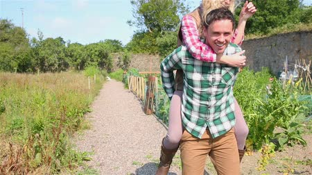 transportar : Handsome man giving piggy back to his pretty girlfriend after gardening together Stock Footage