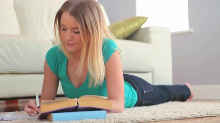 ручки : Pretty young blonde studying while lying in her living room