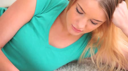 ручки : Concentrated young blonde writing on her notebook while lying in her living room Стоковые видеозаписи