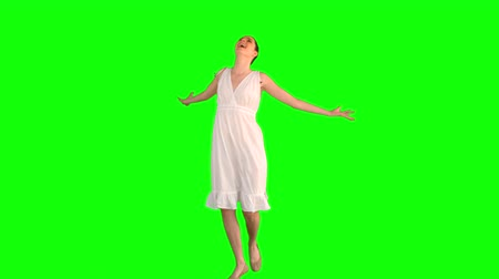 eleganckie : Cheerful model in white dress turning round on green background Wideo