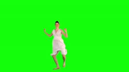 brown dress : Happy model in white dress jumping on green background