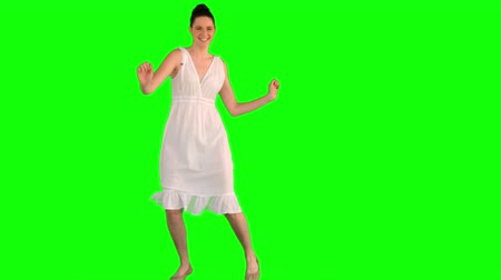 brown dress : Happy model in white dress dancing on green background Stock Footage