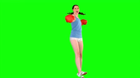 vysoká klíč : Energetic model with boxing gloves spinning round on green background