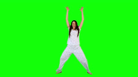 vysoká klíč : Energetic young model in pyjamas exercising on green background Dostupné videozáznamy