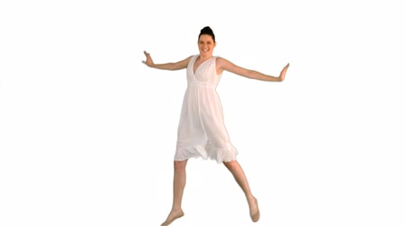vysoká klíč : Cheerful young woman in white dress jumping on white background