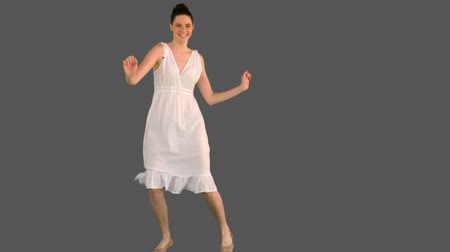 brown dress : Elegant young woman in white dress dancing on grey background