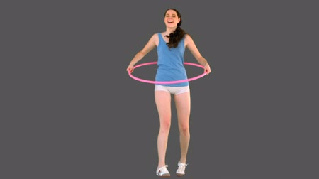 vékony : Young model in sportswear exercising with hula hoop on grey background Stock mozgókép