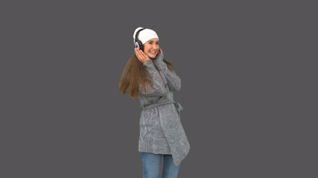 наушники : Cheerful young model in winter clothes listening to music on grey background