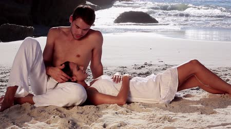okşayarak : Woman with head on the knee of her boyfriend relaxing on the beach Stok Video