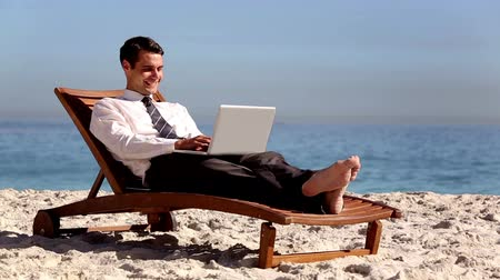 male : Unstressed businessman using laptop on the beach laying on a deck chair