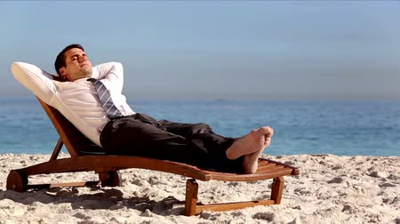 pihenő : Unstressed businessman relaxing on the beach on a deck chair