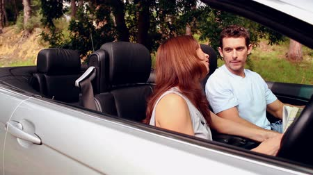discussão : Lost couple arguing and looking at a road map in a convertible car