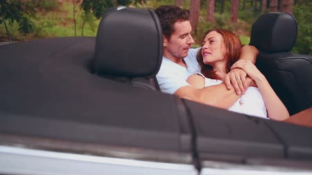 csókolózás : Man kissing his girlfriend in a convertible car while she is lying on him